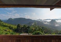 Sikten från fönster ser berget och liten dimma Arkivbild