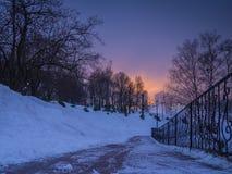 Sikten från snö-täckt parkerar på ljusen för aftonen för stads` s Arkivbild
