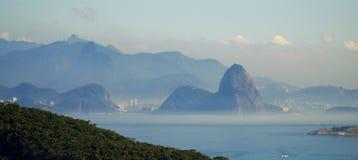 Sikten in mot det Rio de Janeiro och Sugar Loaf berget från Itacoatiara i Niteroi, Brasilien Royaltyfri Bild