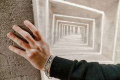 Sikten på caucasian mans handen med armband trycker på väggen Honom stå, titt och som tänker om framtid och val av riktningen royaltyfria bilder