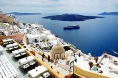 Sikten på den Fira staden och turister som tycker om deras semester Arkivbilder
