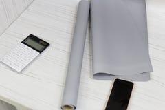 Sikten på den vita trätabellen med rullar och ark av dekorativt papper, vände på räknemaskinen och telefonen Inre av verkligt royaltyfria foton