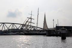 Sikten på modern brokonstruktion med seglar i bakgrunden på floden i amsterdam Nederländerna arkivbild