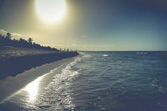 Sikten på stranden på solnedgången med ungar spelar fotboll Arkivfoto