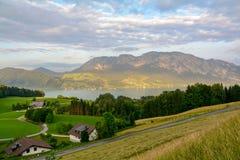 Sikten till sjön Attersee med gräsplan betar ängar och fjällängbergskedja nära Nussdorf Salzburg, Österrike fotografering för bildbyråer