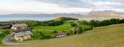 Sikten till sjön Attersee med gräsplan betar ängar och fjällängbergskedja nära Nussdorf Salzburg, Österrike royaltyfri fotografi