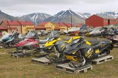 Sikten till snövesslorna parkerade yttersidan för en kort arktisk sommar i Longyearbyen, Norge Arkivfoto
