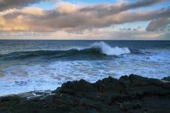 Sikter av havet och svartlavan vaggar på solnedgången Arkivfoton