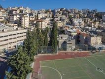 Sikter av moderna byggnader och forntida Nazareth Stadium på en solig dag Arkivfoto