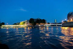 Sikter från Seinen rive och den helgonAgoustin ön på natten Arkivfoto