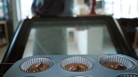 Siktsinsida: öppen ugn för ung kvinna och sätta i bakplåten för muffin Kvinnlig dans, medan vänta efterrätterna lager videofilmer