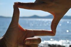 Siktsupphittare från händer med havssikt Royaltyfria Bilder