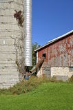 Silage auger leads into old barn Royalty Free Stock Photography