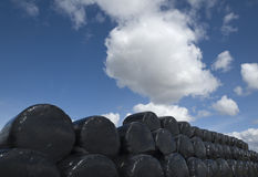 Silage sacks. View of a stack of black, cylindrical-shaped silage sacks at edge of field of farm contrasting against blue sky with white cloud Royalty Free Stock Image