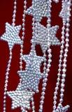 Silber spielt Girlande auf rotem Hintergrund die Hauptrolle Stockfoto