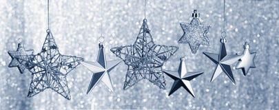 Silber-Sterne, die gegen Funkeln-Hintergrund hängen Lizenzfreie Stockfotografie