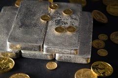 Silberbarren mit Goldmünzen auf schwarzem Hintergrund Lizenzfreie Stockfotografie