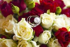 Silberhochzeitringe auf Hochzeitsblumenstrauß von roten und weißen Rosen Stockfotos