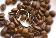 Silberhochzeitringe auf Kaffeebohnen Stockfotos
