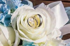 Silberhochzeitringe sind auf Blumenblättern von künstlichem stiegen Lizenzfreies Stockfoto
