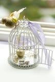 Silberhochzeitringe und Verlobungsring im dekorativen Käfig des Vogels Stockbild