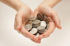 Silbermünzen in den Händen Stockfotos