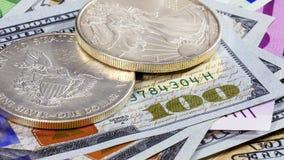Silberne amerikanische Dollarmünzen über verschiedenen Banknoten Lizenzfreies Stockfoto