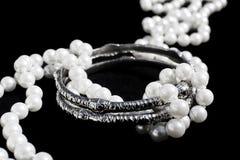Silberne Armbänder und Perlen Stockfotos