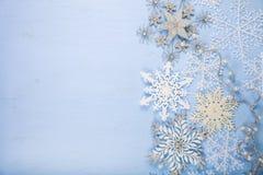 Silberne dekorative Schneeflocken auf einem blauen hölzernen Hintergrund christ Stockfotografie