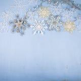 Silberne dekorative Schneeflocken auf einem blauen hölzernen Hintergrund christ Stockfotos