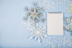 Silberne dekorative Schneeflocken und ein Notizbuch auf einem blauen hölzernen BAC Stockbild