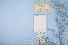 Silberne dekorative Schneeflocken und ein Notizbuch auf einem blauen hölzernen BAC Lizenzfreie Stockfotos