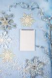 Silberne dekorative Schneeflocken und ein Notizbuch auf einem blauen hölzernen BAC Lizenzfreie Stockfotografie
