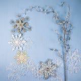 Silberne dekorative Schneeflocken und Niederlassung auf einem blauen hölzernen backgro Stockfotos