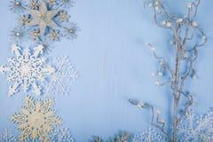 Silberne dekorative Schneeflocken und Niederlassung auf einem blauen hölzernen backgro Stockfotografie