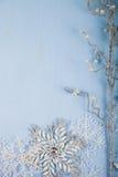 Silberne dekorative Schneeflocken und Niederlassung auf einem blauen hölzernen backgro Stockbild