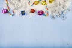 Silberne dekorative Schneeflocken und Schnee auf einem blauen hölzernen backgroun Lizenzfreie Stockfotografie