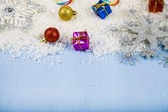 Silberne dekorative Schneeflocken und Schnee auf einem blauen hölzernen backgroun Lizenzfreie Stockbilder