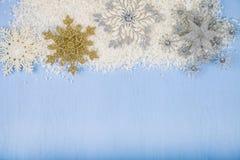 Silberne dekorative Schneeflocken und Schnee auf einem blauen hölzernen backgroun Stockfotos