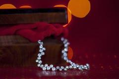Silberne Diamantkette in einer schönen hölzernen Schatulle mit rotem Hintergrund Stockfotos