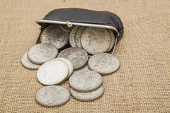 Silberne Dollar verschüttete Münzengeldbeutelhintergrund Lizenzfreie Stockfotos