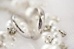 Silberne einfache Eheringe, Perlen und Bergkristalle Stockfotografie