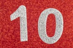 Silberne Farbe der Nr. zehn über einem roten Hintergrund jahrestag Lizenzfreie Stockfotos
