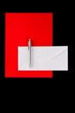 Silberne Feder auf einem weißen Umschlag mit rotem Papier Stockbild