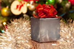 Silberne Geschenkbox mit rotem Band auf festlichem Hintergrund Lizenzfreie Stockfotos