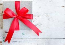 Silberne Geschenkbox mit rotem Bandbogen auf Weinlesehintergrund Stockfotografie