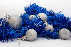 Silberne glänzende Weihnachtsbälle und glänzendes blaues Band auf weißem Hintergrund Lizenzfreie Stockbilder