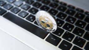 Silberne Goldkräuselungsmünze auf einer Laptoptastaturnahaufnahme Blockchain-Bergbau Digital-Geld und virtuelles cryptocurrency Stockfotos
