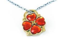 Silberne Halskette mit den hängenden und roten Edelsteinen des Klees Lizenzfreies Stockfoto