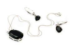 Silberne Halskette mit schwarzem Anhänger u. Ohrringisolator Stockfotografie